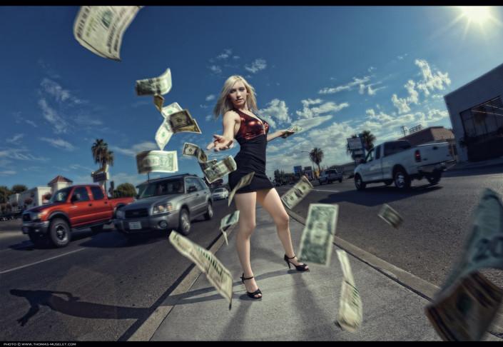 photo d'une femme sexy qui jète des dollars dans une rue