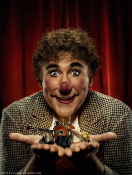 un grand clown photographié avec des instruments miniatures