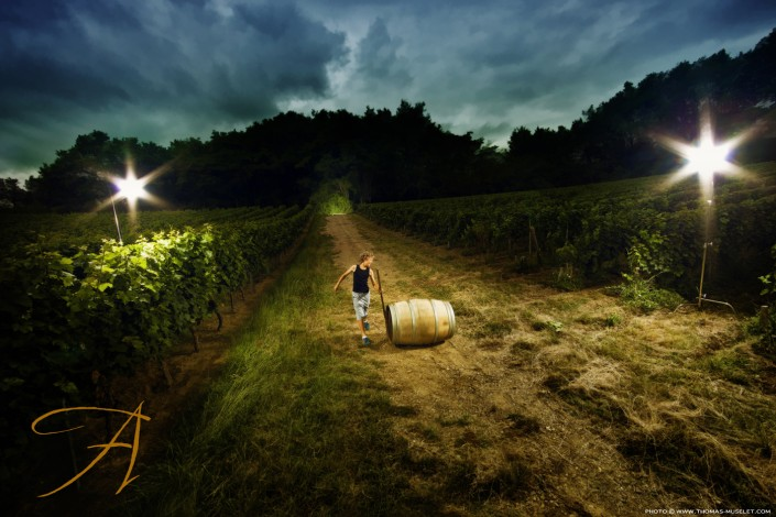 un enfant qui court à coté de tonneaux de Vin