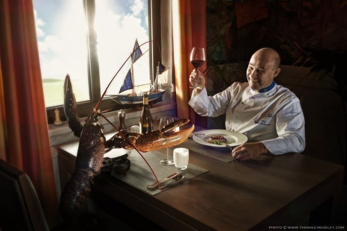 Un cuisinier qui mange avec un Homard.