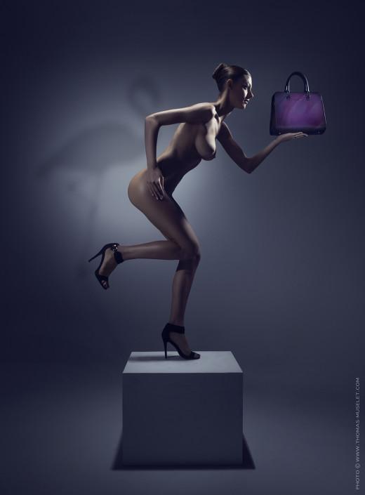 photo d'une femme nue tenant un sac à main. photo de mode originale avec femme sexy