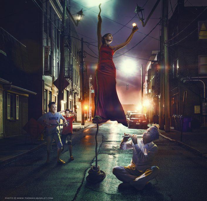 photo d'une magicienne qui grimpe à la corde en pleine rue