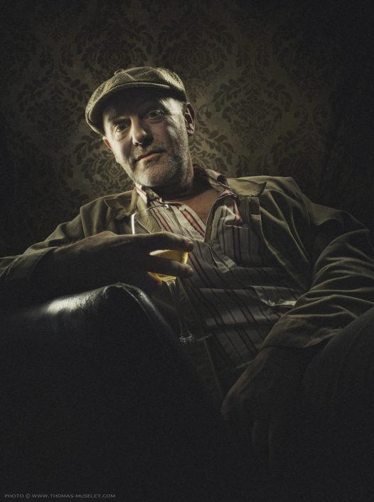 photo de Jacques Bonnaffé dans un fauteuil avec un verre de vin