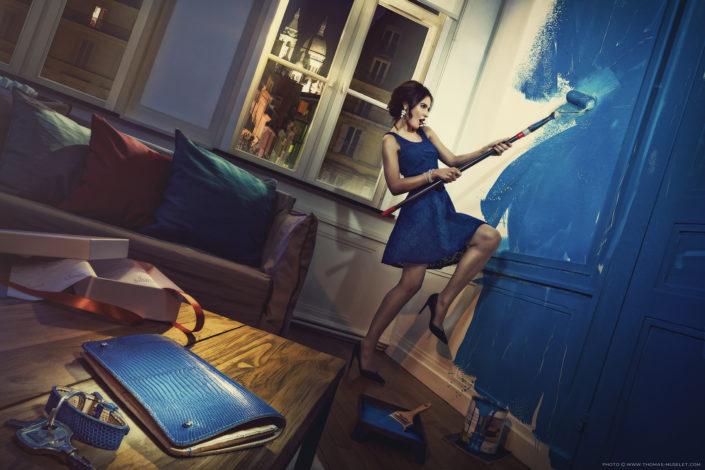 photo artistique d'une femme qui étale de la peinture bleu sur un mur